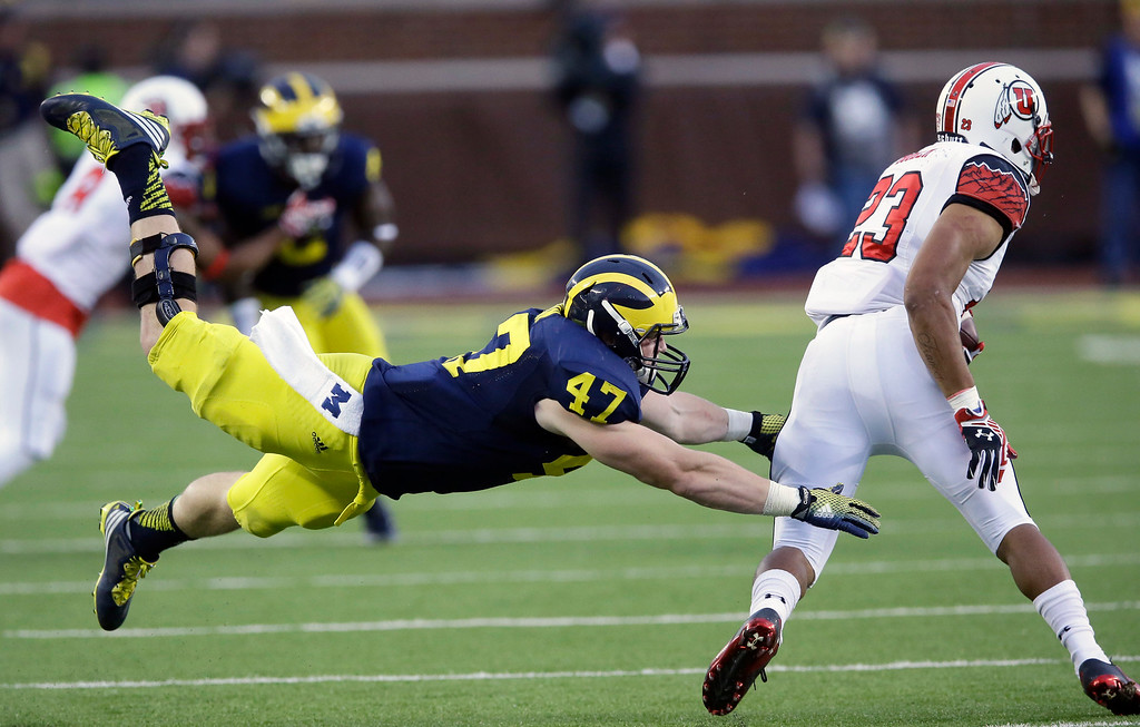 . Michigan linebacker Jake Ryan (47) reaches in on Utah running back Devontae Booker (23) during the second half of an NCAA college football game in Ann Arbor, Mich., Saturday, Sept. 20, 2014. (AP Photo/Carlos Osorio)