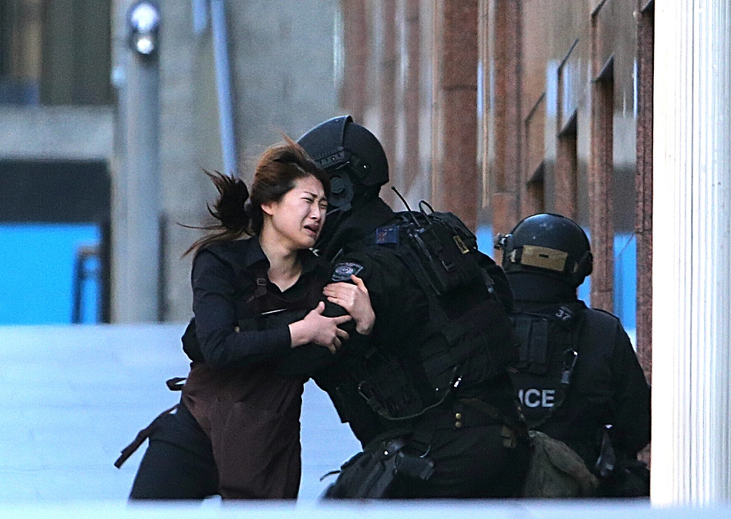 . A hostage runs to armed tactical response police officers for safety after she escaped from a cafe under siege at Martin Place in the central business district of Sydney, Australia, Monday, Dec. 15, 2014. New South Wales state police would not say what was happening inside the cafe or whether hostages were being held. But television footage shot through the cafe\'s windows showed several people with their arms in the air. (AP Photo/Rob Griffith)