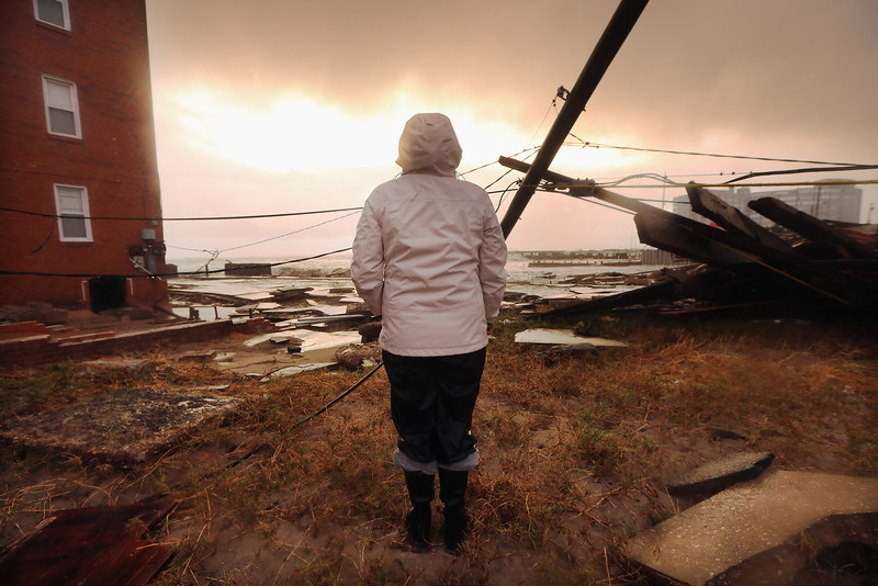 . Resident Kim Johnson inspects the area around her apartment building (L) which flooded and destroyed large sections of an old boardwalk, on October 30, 2012 in Atlantic City, New Jersey. Johnson fled the area when the water began to rise yesterday.  The storm has claimed at least 16 lives in the United States, and has caused massive flooding accross much of the Atlantic seaboard. US President Barack Obama has declared the situation a \'major disaster\' for large areas of the US East Coast including New York City. (Photo by Mario Tama/Getty Images)