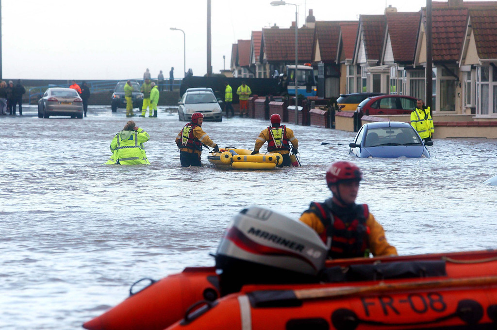 . People are rescued by the Royal National Lifeboat Institution (RNLI) from the floods as heavy seas and high tides sweep across the country in in Rhyl, Britain, 05 December 2013.  EPA/PETER BYRNE