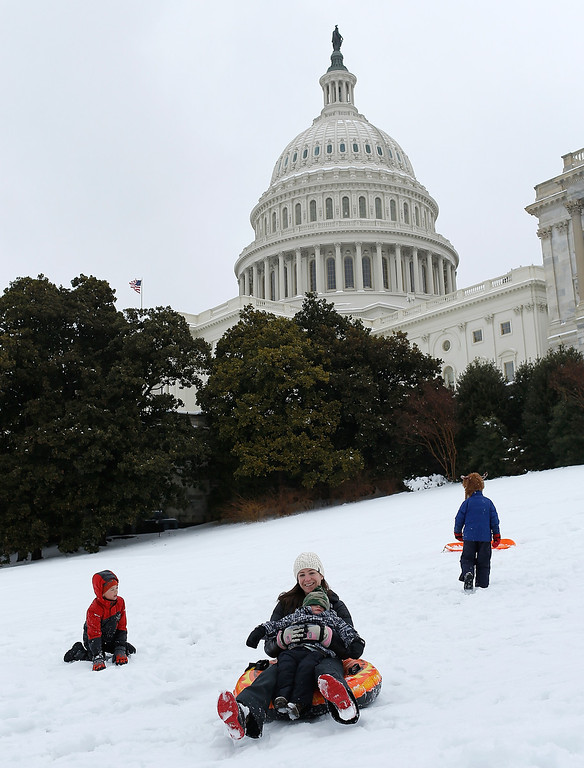 . Members of the Miller family sled on the west lawn of the U.S. Capitol February 13, 2014 in Washington, DC. The east coast of the U.S. was hit with a winter storm leaving up to 12 inches of snow on the ground in parts of the Washington, DC area.  (Photo by Win McNamee/Getty Images)
