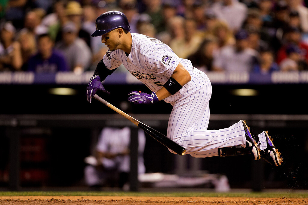 . DENVER, CO - JULY 19:  Carlos Gonzalez #5 of the Colorado Rockies trips while attempting to bunt in the seventh inning against the Chicago Cubs at Coors Field on July 19, 2013 in Denver, Colorado.  Gonzales went on to strike out in the at-bat. (Photo by Justin Edmonds/Getty Images)