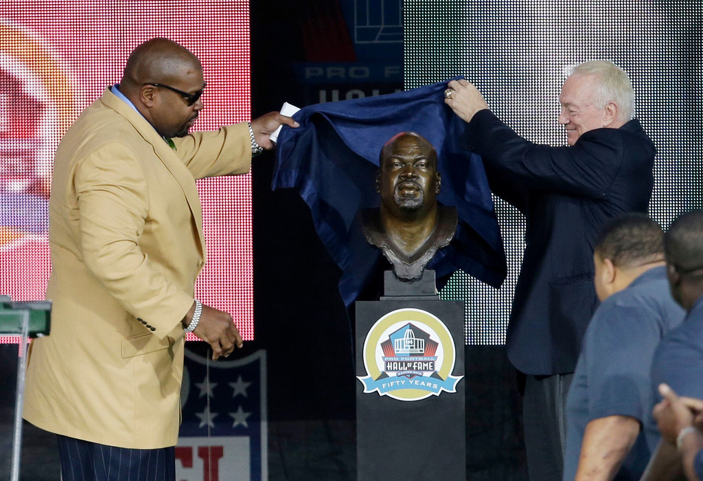 . Former NFL football player Larry Allen, left, and Dallas Cowboys owner Jerry Jones unveil the bust of Allen during the induction ceremony at the Pro Football Hall of Fame Saturday, Aug. 3, 2013, in Canton, Ohio. (AP Photo/Tony Dejak)