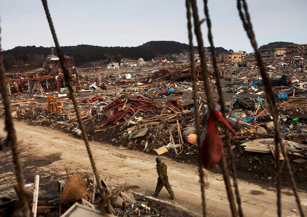 . FILE - In this Tuesday, March 22, 2011, file photo, a Japanese soldier walks down a path in the earthquake and tsunami-destroyed town of Shizugawa, northeastern Japan. Japan marks four years since the earthquake, tsunami, and nuclear disaster on Wednesday, March 11, 2015. (AP Photo/David Guttenfelder, File)