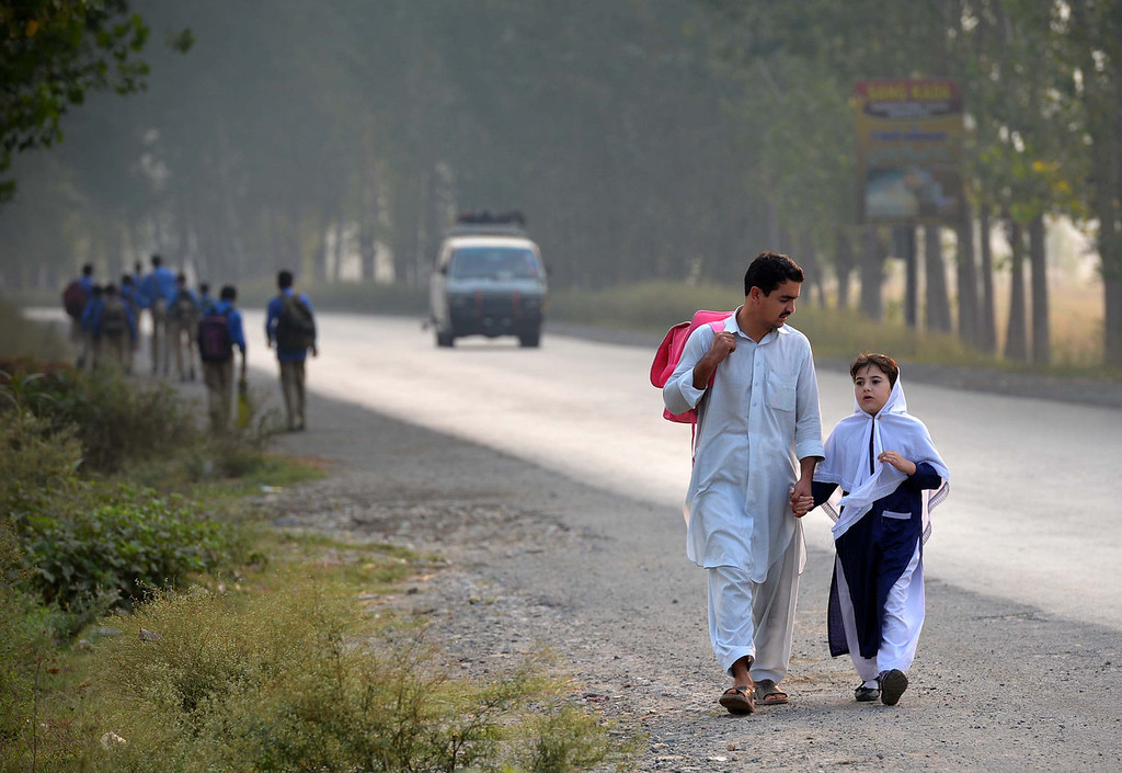 . A Pakistani schoolgirl holds the hand of a relative as they walk down a road following the end of class in Mingora, a town in Swat valley, on October 9, 2013, the first anniversary of the shooting of Malala Yousafzai by the Taliban. Yousafzai, the teenage activist nominated for the Nobel Peace Prize, says she has not done enough to deserve the award, as her old school closed October 9 to mark the first anniversary of her shooting by the Taliban. A Majeed/AFP/Getty Images