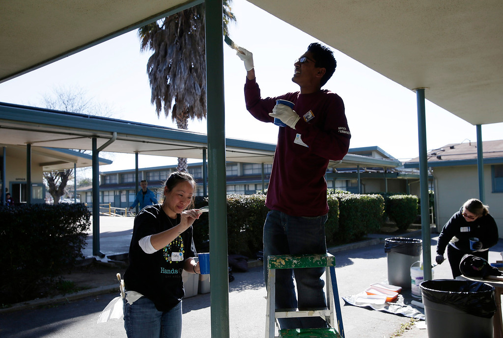 . Kaiser Permanente volunteers, Kathy Ho and Thomas Ryan paint the hallway poles at Ryan Elementary School during a Dr. Martin Luther King Jr. day-of-service activity in San Jose, Calif. on Monday, January 21, 2013.   (Gary Reyes/ Staff)
