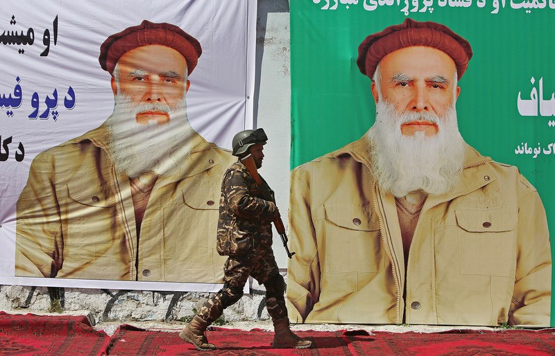 . An Afghan security man walks past election posters of presidential candidate Abdul Rasoul Sayyaf, during a campaign rally in Jalalabad, east of Kabul, Afghanistan, Tuesday, April 1, 2014. Eight Afghan presidential candidates are campaigning for the third presidential election. Elections will take place on April 5, 2014. (AP Photo/Rahmat Gul)
