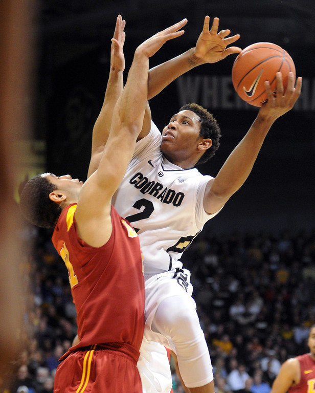 . Xavier Johnson of Colorado goes to the basket on Aaron Fuller of Southern California during the first half of the January 10, 2013 game in Boulder.  Cliff Grassmick/Daily Camera