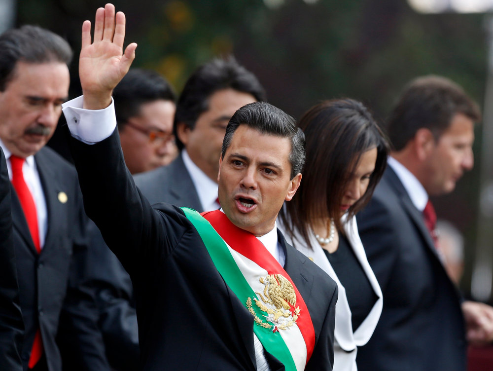 . Mexico\'s new President Enrique Pena Nieto waves after taking oath in congress in Mexico City December 1, 2012.    Enrique Pena Nieto took over as Mexican president on Saturday, offering a shot at redemption for the party that shaped modern Mexico if he can bring an end to years of violence and economic underperformance.      REUTERS/Bernardo Montoya