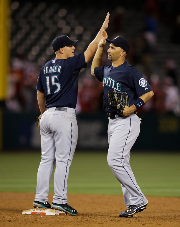 . Seattle Mariners\' Raul Ibanez, right, and Kyle Seager celebrate their team\'s 3-2 win against the Los Angeles Angels after the 10th inning of a baseball game in Anaheim, Calif., Tuesday, June 18, 2013. (AP Photo/Jae C. Hong)