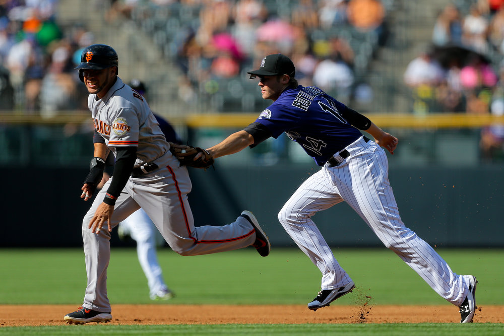 . Josh Rutledge #14 of the Colorado Rockies tags out Gregor Blanco #7 of the San Francisco Giants for an out during the first inning at Coors Field on September 1, 2014 in Denver, Colorado. (Photo by Justin Edmonds/Getty Images)