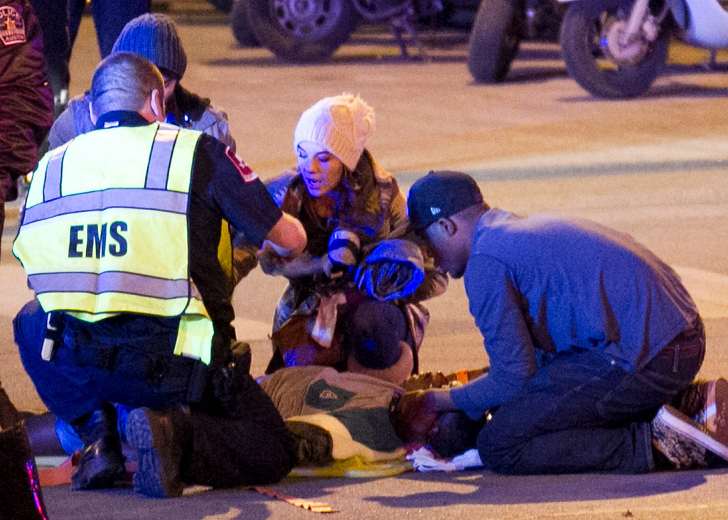 . Bystanders and paramedics tend to a person who was struck by a vehicle on Red River Street in downtown Austin, Texas, at SXSW on Wednesday, March 12, 2014.  (AP Photo/Austin American-Statesman, Jay Janner)