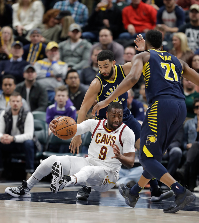 . Cleveland Cavaliers\' Dwyane Wade (9) falls as he is defended by Indiana Pacers\' Cory Joseph and Thaddeus Young (21) during the second half of an NBA basketball game Friday, Dec. 8, 2017, in Indianapolis. The Pacers won 106-102. (AP Photo/Darron Cummings)