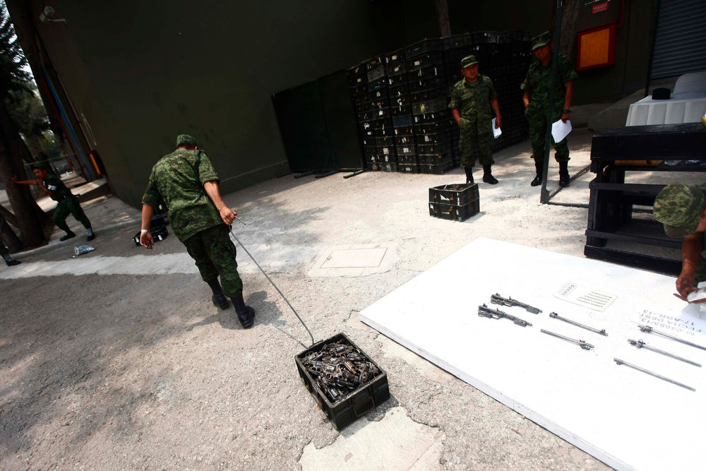 . A soldier drags a crate of weapons, that were confiscated by national security authorities, after they were destroyed at a military zone of Mexico City April 17, 2013. The military is in charge of storing and destroying weapons, not only those handed in by the civilian population sometimes including those inherited from an ancestor who might have fought in the revolution but also the weapons confiscated in the six-year-long, ongoing drug war that has so far killed some 70,000 people. Picture taken April 17, 2013. REUTERS/Edgard Garrido