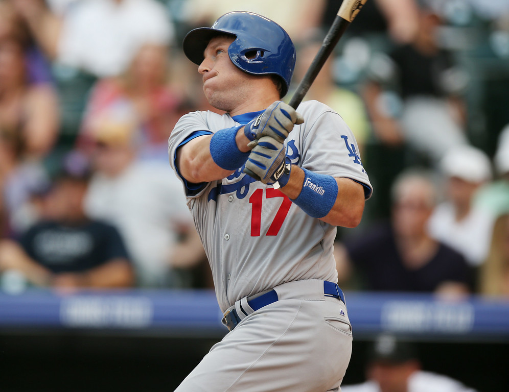 . Los Angeles Dodgers\' A.J. Ellis follows the flight of his sacrifice fly to drive in a run against the Colorado Rockies in the fourth inning of a baseball game in Denver on Thursday, July 3, 2014. (AP Photo/David Zalubowski)