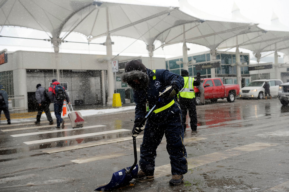 . A member of the grounds crew shovels slush in front of the East Terminal at Denver International Airport on Sunday, February, 24, 2013. A major winter storm caused the cancellation of nearly 200 flights at DIA on Sunday. Seth A. McConnell, The Denver Post