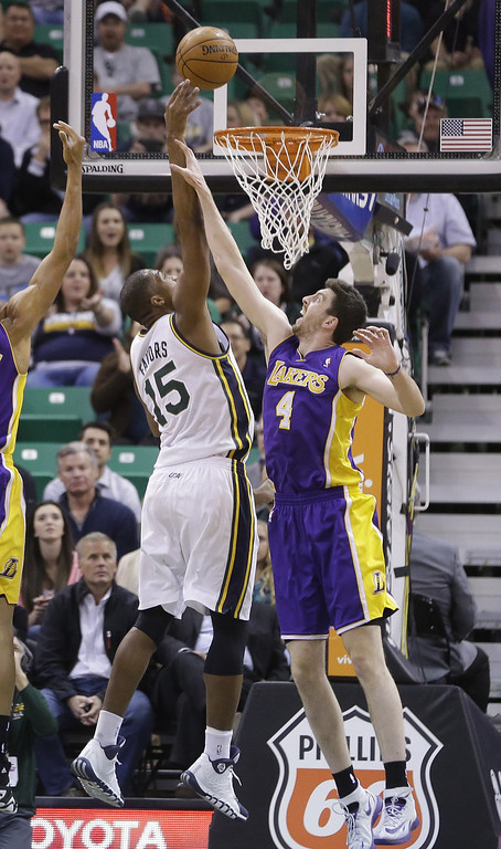 . Los Angeles Lakers Ryan Kelly (4) defends against Utah Jazz\'s Derrick Favors (15) in the first quarter during an NBA basketball game Monday, April 14, 2014, in Salt Lake City, Utah. (AP Photo/Rick Bowmer)