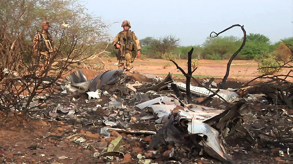 ". A handout photo released on July 25, 2014 by ECPAD shows French soldiers standing by the wreckage of the Air Algerie flight AH5017 which crashed in Mali\'s Gossi region, west of Gao, on July 24. The first images of the Air Algerie crash site in Mali emerged on July 25, showing a stark terrain littered with bits of a plane that appears to have been pulverized on impact. France announced there were no survivors among the 118 people on board the Air Algerie flight that crashed over Mali, saying bad weather was the likely cause of the disaster. AFP PHOTO / ECPAD   RESTRICTED TO EDITORIAL USE - MANDATORY CREDIT ""AFP PHOTO / ECPAD\"" - NO MARKETING NO ADVERTISING CAMPAIGNS NO ARCHIVES - DISTRIBUTED AS A SERVICE TO CLIENTS - TO BE USED WITHIN 30 DAYS FROM JULY 25, 2014-/AFP/Getty Images"