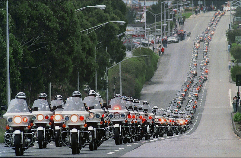 A line of motorcycle officers stretching a mile long leads the funeral procession for slain Millbrae police officer David Chetcuti along El Camino Real in South San Francisco.