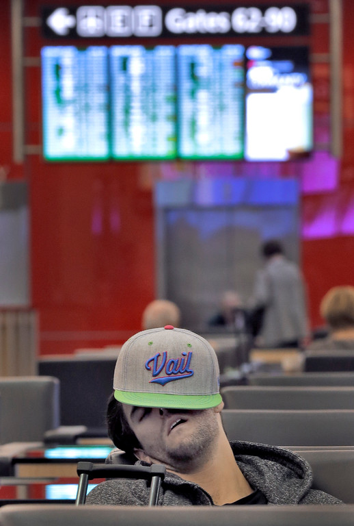 . A passenger sleeps while waiting for a flight Tuesday, Jan. 27, 2015, at the Tampa International Airport in Tampa, Fla. Most flights out of Tampa to the northeast are canceled due to major storm dumping several inches of snow in the area. (AP Photo/Chris O\'Meara)
