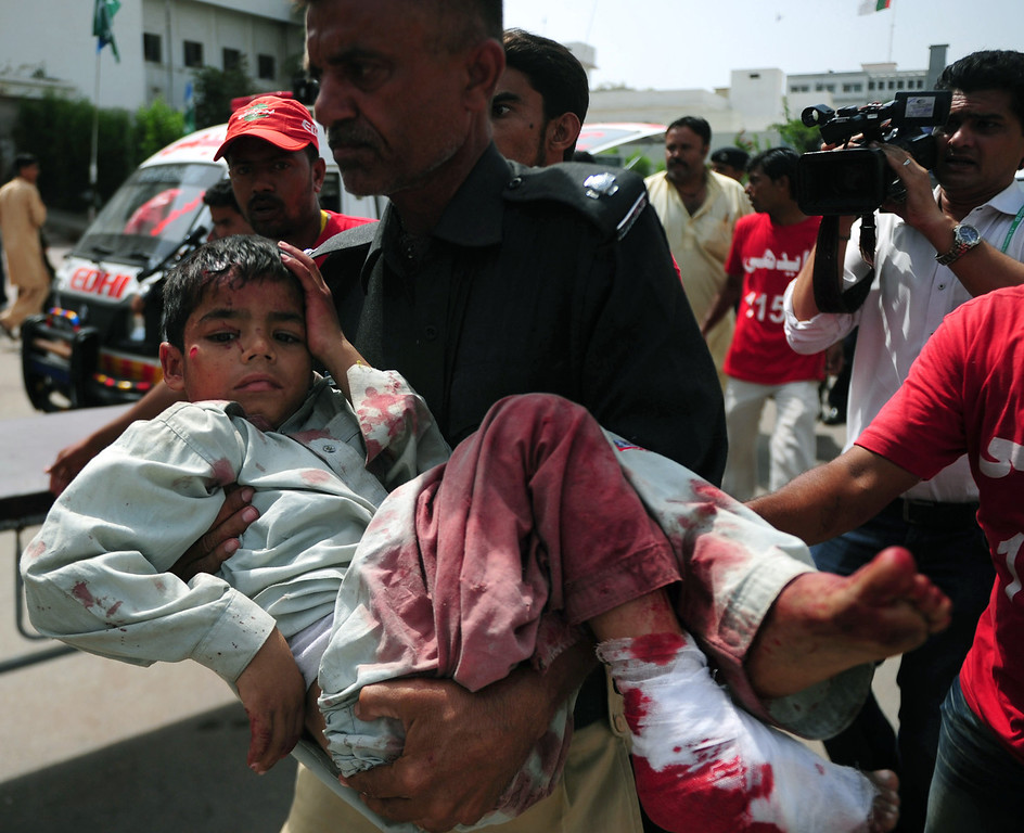 . A Pakistani police officer carries an injured blast victim at a hospital following a bomb explosion in Karachi on May 11, 2013. A Taliban bomb attack targeting an election candidate killed at least 11 people and wounded 36 others in Pakistan\'s financial hub of Karachi as polls got under way, a doctor said. The bomb targeted a candidate seeking election to the Sindh provincial assembly for the Awami National Party (ANP), the main secular party for ethnic Pashtuns, police said. RIZWAN TABASSUM/AFP/Getty Images