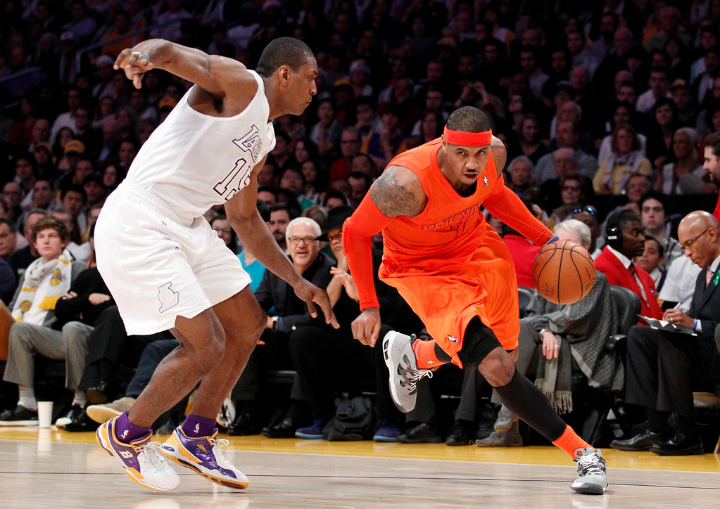 . New York Knicks\' Carmelo Anthony (R) dribbles the ball as Los Angeles Lakers\' Metta World Peace defends during the first half of their NBA basketball game in Los Angeles December 25, 2012. REUTERS/Danny Moloshok