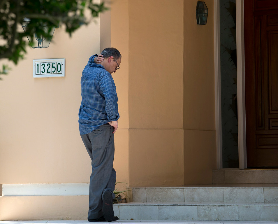 . An unidentified man waits to enter the home of the family of journalist Steven Sotloff, Tuesday, Sept. 2, 2014 in Pinecrest, Fla. An Internet video posted online Tuesday purported to show the beheading by the Islamic State group of Sotloff, who went missing in Syria last year. (AP Photo/Wilfredo Lee)