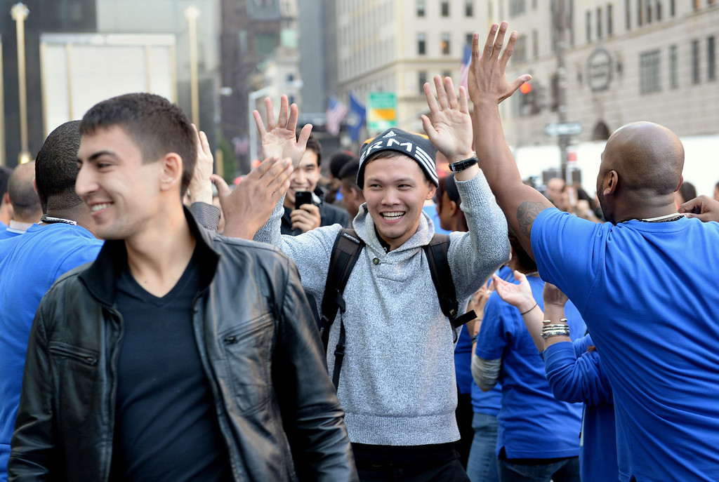 . Customers waiting to buy the Apple iPhone 5 are greeted by employees at the Apple Store on Fifth Avenue September 20, 2013 in New York. Some waited as long as fifteen days in line outside the store to be the first to buy the phone. AFP PHOTO/Stan HONDA/AFP/Getty Images