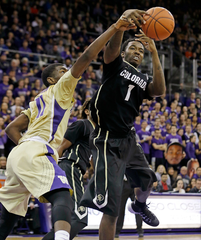 . Washington\'s Mike Anderson, left, knocks the ball away from Colorado\'s Wesley Gordon in the second half of an NCAA college basketball game, Sunday, Jan. 12, 2014, in Seattle. Washington won 71-54. (AP Photo/Elaine Thompson)
