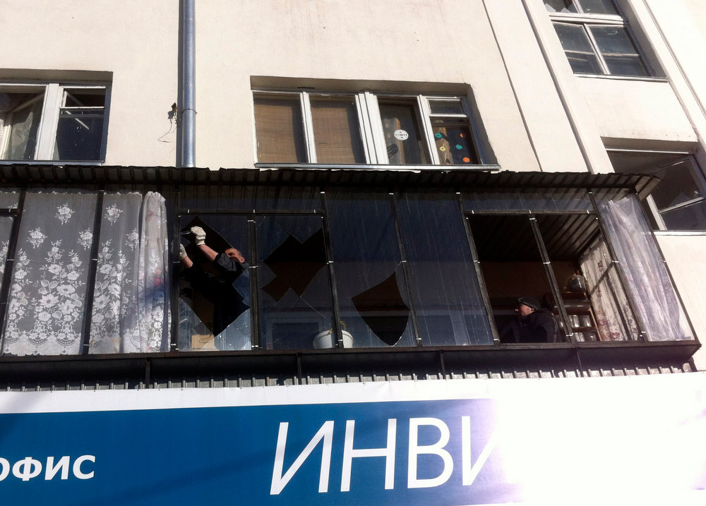 Description of . A man removes shards of glass from the frame of a broken window following sightings of a falling object in the sky in the Urals city of Chelyabinsk February 15, 2013. A powerful blast rocked the Russian region of the Urals early on Friday with bright objects, identified as possible meteorites, falling from the sky, emergency officials said. REUTERS/Andrei Kuzmin