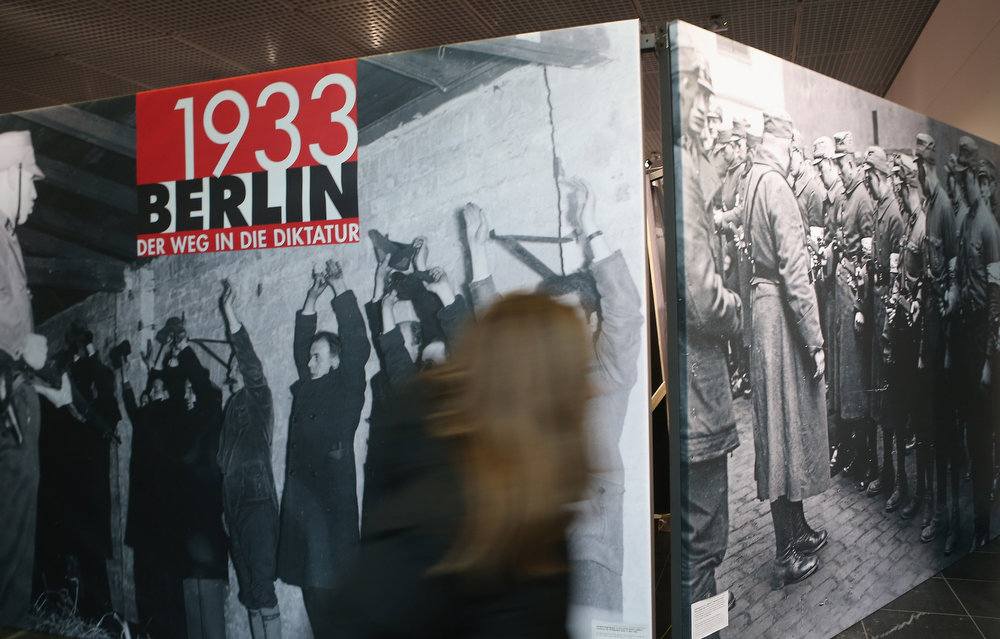 Description of . A visitor looks at passes by historical photographs at the exhibition