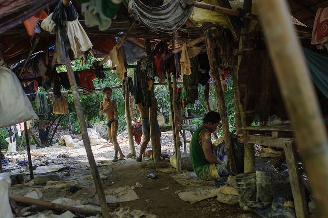 . A miner stands in a mountain-side mining camp in his underwear, having just washed the tunnel mud off himself during their midday break, on April 22, 2014 in Pinut-An, Philippines. (Photo by Luc Forsyth/Getty Images)