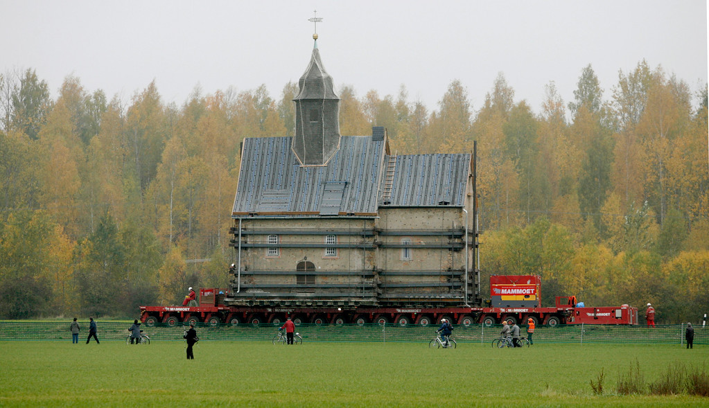 . The Emmaus church is transported on a special trailer, after leaving the eastern German village of Heuersdorf October 25, 2007. The church, built in 1297, will be moved over 12 kilometers to the neighboring town of Borna, as Heuersdorf has to give way for the extension of an opencast lignite mine.    REUTERS/Arnd Wiegmann