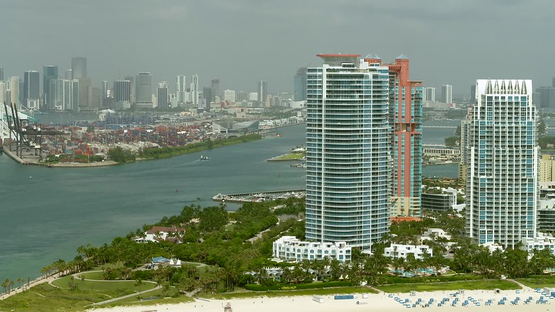Aerial Miami Beach epic shot of coastal architecture and park inlet port and Downtown in background