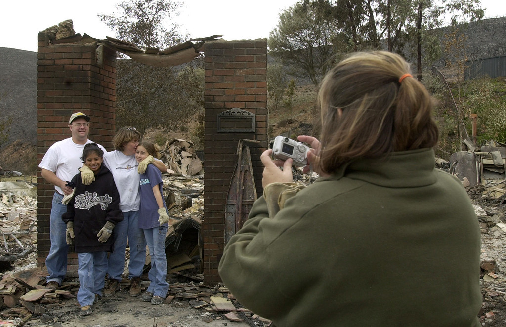 . A family friend takes a photo of the Shalinsky family -- David, left, Emily, Janet and Claire, right -- in front of their burned-out home in the Scripps Ranch area of San Diego, Calif. Thursday, Oct. 30, 2003. The home was among more than 1,000 lost in the 270,000 acre Cedar fire. (AP Photo/Charlie Riedel)