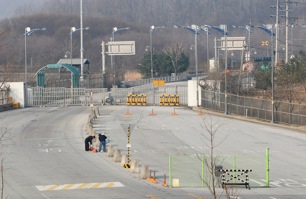 . Workers clean up the empty road at the customs, immigration and quarantine office in Paju, South Korea, near the border village of Panmunjom, Thursday, April 4, 2013. North Korea on Wednesday barred South Korean workers from entering a jointly run factory park just over the heavily armed border in the North, officials in Seoul said, a day after Pyongyang announced it would restart its long-shuttered plutonium reactor and increase production of nuclear weapons material. (AP Photo/Ahn Young-joon)