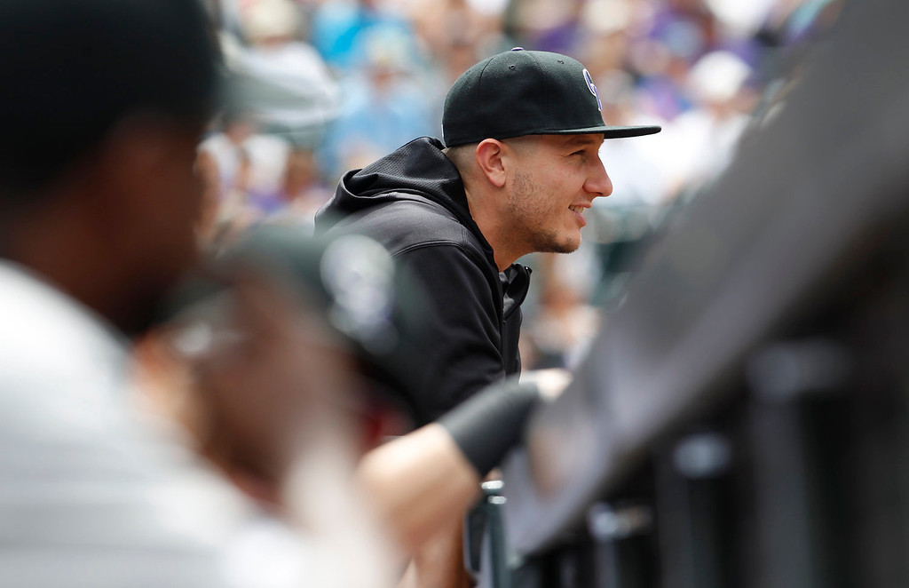 . Colorado Rockies shortstop Troy Tulowitzki, who has been sidelined by a broken rib, looks on against the San Francisco Giants in the first inning of a baseball game in Denver on Sunday, June 30, 2013.  (AP Photo/David Zalubowski)