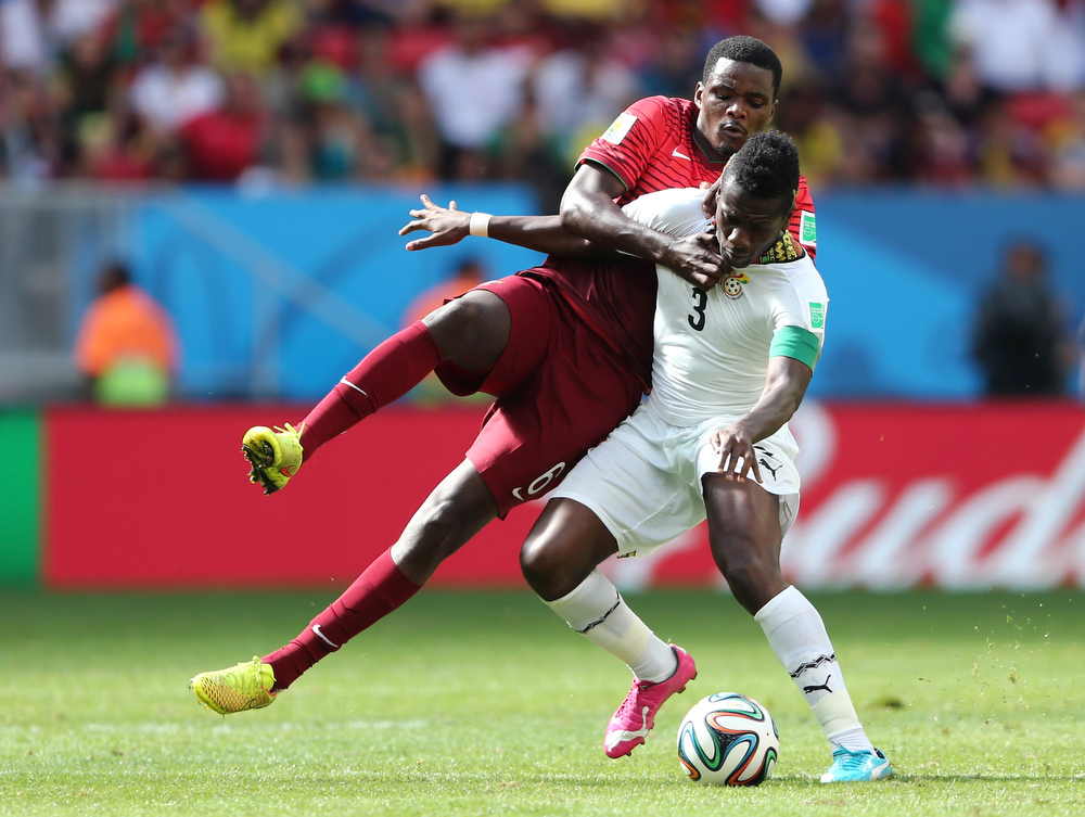 . William Carvalho of Portugal challenges Asamoah Gyan of Ghana during the 2014 FIFA World Cup Brazil Group G match between Portugal and Ghana at Estadio Nacional on June 26, 2014 in Brasilia, Brazil.  (Photo by Warren Little/Getty Images)