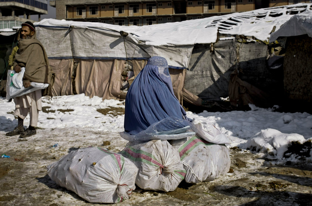 Description of . An Afghan displaced woman sits on bags filled with fire wood provided by a German run charity organization at a refugee camp in Kabul, Afghanistan, Tuesday, Dec. 18, 2012. A German run charity organization, known as Johanniter, distributed winter relief assistance to some 279 internally displaced families in Kabul. (AP Photo/Musadeq Sadeq)