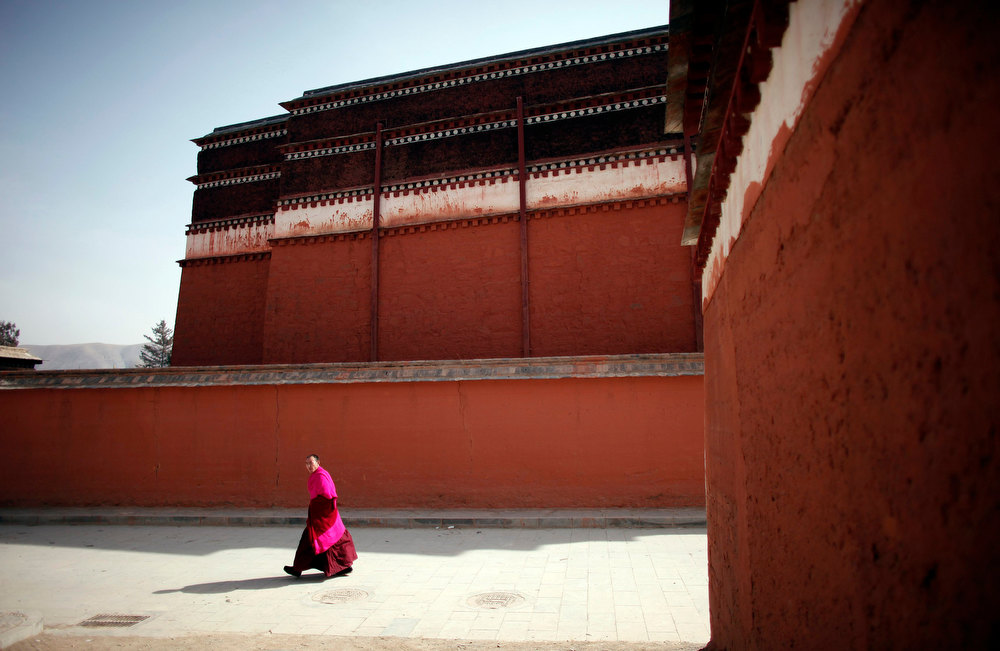 Description of . A Tibetan monk walks the grounds in Labrang Monastery during Tibetan new year, in Xiahe county, Gansu Province, February 11, 2013. Tibetans in a northwest part of China which has been a focus of self-immolation protests against Chinese rule marked a low-key lunar New Year on Monday, with many saying celebrations were inappropriate while the burnings continued. At least 20 people have set themselves on fire in the region around Xiahe in Gansu province over the last year, according to exiles and rights groups. Xiahe is home to a large ethnically Tibetan population and also to the monastery at Labrang, one of the most important centres for Tibetan Buddhism. The Tibetan lunar new year is supposed to be a time for celebration, but many Tibetans who spoke to Reuters in Xiahe said there would be no entertainment this year.  REUTERS/Carlos Barria