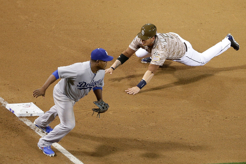 . San Diego Padres\' Yasmani Grandal, right, safely steals third base as Los Angeles Dodgers third baseman Juan Uribe moves off the base during the eighth inning during an opening night baseball game on Sunday, March 30, 2014, in San Diego. (AP Photo/Gregory Bull)