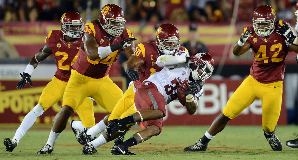 . USC defenders swarm Washington State\'s Teondray Caldwell #34 during their game at the Los Angeles Memorial Coliseum  Saturday, September 7, 2013.  (Photo by Hans Gutknecht/Los Angeles Daily News)