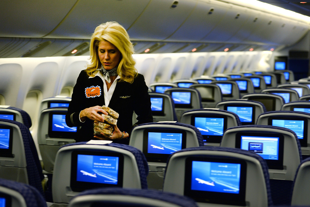 . United flight attendant Nancy Novelli puts peanut butter and jelly sandwiches on the seats of all of the players aboard the Denver Broncos United plane prior to them arriving at Denver International Airport in Denver, Co on January 26, 2014.  The Denver Broncos team flew out on the United charter plane to head to New Jersey for the Super Bowl in New Jersey.  (Photo By Helen H. Richardson/ The Denver Post)