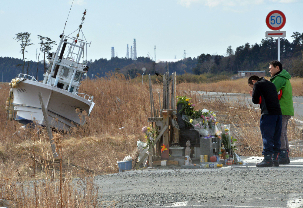 . Two men offer prayers before the altar at Namie, near the striken TEPCO\'s Fukushima Dai-ichi nuclear plant in Fukushima prefecture on March 11, 2014 on the third anniversary day of massive earthquake and tsunami hit northern Japan. The 9.0 magnitude earthquake in 2011 sent a huge wall of water into the coast of the Tohoku region, splintering whole communities, ruining swathes of prime farmland and killing nearly 19,000 people. (YOSHIKAZU TSUNO/AFP/Getty Images)