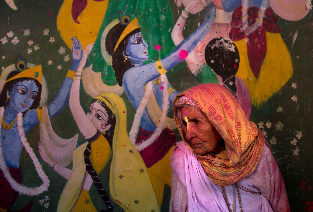 . An Indian widow walks past the painting of Lord Krishna and his concert Radha during Holi, the arrival of spring festival at the Gopinath temple in Vrindavan, 180 kilometers (112 miles) south-east of New Delhi, India, Thursday, March 9, 2017. Up to just a few years ago this joyful celebration was forbidden for Hindu widows. Like hundreds of thousands of observant Hindu women, they would have been expected to live out their days in quiet worship, dressed only in white, with their very presence being considered inauspicious for all religious festivities. (AP Photo /Manish Swarup)