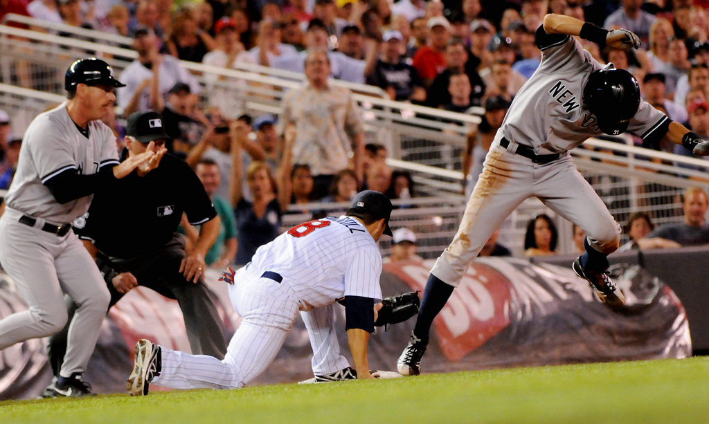 . New York right fielder Ichiro Suzuki safely reaches third as he beats the tag by Minnesota third baseman Jamey Carroll during the eighth inning. (Pioneer Press: John Autey)