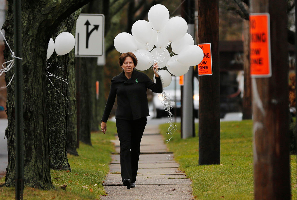 Description of . A woman carries balloons to the Abraham L. Green & Sons Funeral Home, where Sandy Hook Elementary school victim Noah Pozner's funeral will be held, in Fairfield, Connecticut December 17, 2012.  REUTERS/Shannon Stapleton