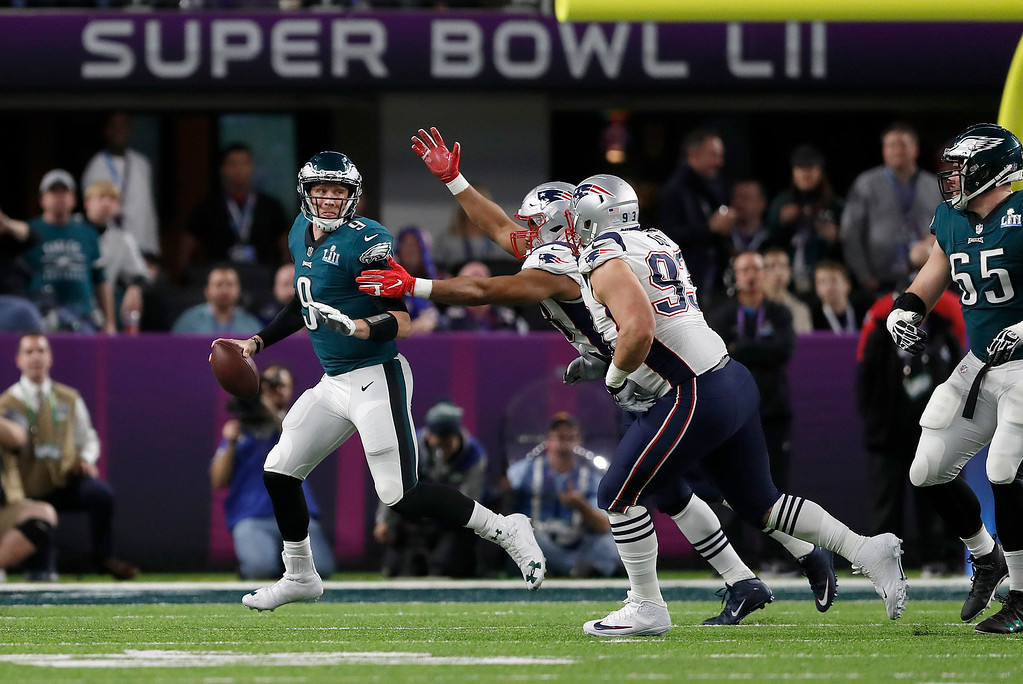 . Philadelphia Eagles\' Nick Foles is pressured by New England Patriots defenders during the first half of the NFL Super Bowl 52 football game Sunday, Feb. 4, 2018, in Minneapolis. (AP Photo/Jeff Roberson)