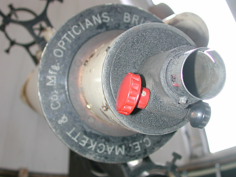"""Here we see that the refractors rack and pinion focuser has been replaced. It is an A. Jaegers focuser characterized by the bright red focusing knob and orver all design. Over the years the Jaegers focuser wore out and one red knob and pinion gear were replaced by an Edmund Scientific Co. doner. That is why the knob on the right is black! ( The """"doner"""" Edmund telescope is shown in another image.)"""