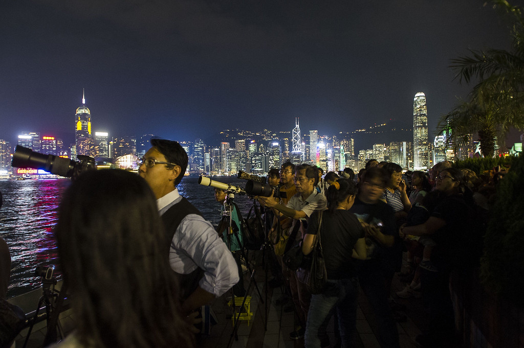 . People take photographs of the lunar eclipse  at The Avenue of Stars in Hong Kong on October 8, 2014.   The total lunar eclipse is the second of two in 2014 and the second in a tetrad (four total lunar eclipses in series).  AFP PHOTO / XAUME  OLLEROS/AFP/Getty Images
